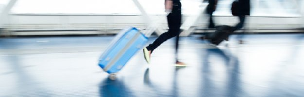 Reisende mit Koffer am Flughafen